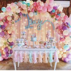 Mesa decorada com bexigas no fundo.