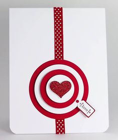 handmade Valentine card by Manitoba Stamper ... red and white ,,, clean and simple ,,, focal point of concentric red and white layered circle bullseyel target with a glittered heart in the center ... thin red ribbon with white polka dots stretches top to bottom ,.. like the tiny jewelry tag with the sentiment  ... great card! ...