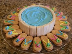 swimming pool cake trimmed with wafer cookies and flip flop cookies made from vienna cookies