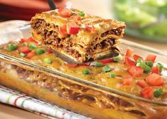 Mexican Lasagna Casserole 1 can (10.75 ounces) condensed cheddar cheese soup 1/4 cup milk 1 package (1 ounce) fajita seasoning mix, divided 1 pound ground beef 1 can (10.75 ounces) condensed golden mushroom soup 1/2 cup water 1 tablespoon chili powder 1 1/2 teaspoons crushed dried oregano leaves 12 (5- to 6-inch diameter) corn tortillas Chopped tomatoes, optional Sliced green onions, optional