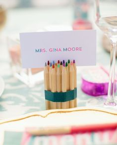 Bundles of colored pencils doubled as place card holders at the place settings of the bride and groom.
