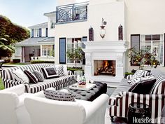 Martyn Lawrence Bullard covered roll-arm sofas and chairs in Perennials fabrics for a black-and-white outdoor living room in a Los Angeles house.