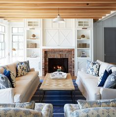 Cottage living room features a pair of white slipcovered sofas adorned with blue pillows facing each other across from a chevron tiled coffee table atop a blue striped rug. Beautiful living room boasts a brick tiled fireplace under an x paneled TV cabinet concealing a flatscreen TV flanked by built-in shelving backed in beadboard.