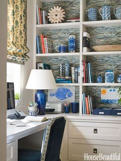 Sleek white desk, lampshade, and paint, plus blue & white wallpaper on the back of the bookcases, blue & ivory Roman shade (and the fabric's border used to trim the chair),  and blue & white tchochkes make a serene place to work. Design: Ann Wolf. Photo: Reed Davis.