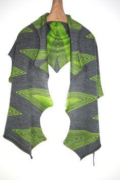 Handgefertigt mit weicher Merinowolle, schmiegt sich dieser sehr fein gestrickte und weiche Schal wunderbar um den Körper. Die Grundfarbe ist Mittelgrau. Die grünen Streifen geben dem Accessoire zusätzlich zur ungewöhnlichen Form, noch eine besondere Note.  Mit diesem gestricktem Tuch können Sie Ihre Garderobe bereichern. Je nach Kleidergröße lässt sich dieses Strickstück um den Körper drapieren, binden, knoten oder mit einem Gürtel oder einer Brosche fixieren. Spielen Sie, experimentieren…