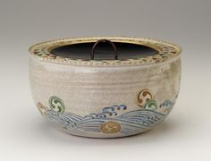 Use of the fanciful motif of crest medallions tossed like foam on rough waves continues the style of enamel decoration invented by the Kyoto potter Ninsei. Many later Kyoto potters executed ceramics using Ninsei's style. | Water jar in style of Nonomura Ninsei late 19th century | Nonomura Ninsei (Japanese, active ca. 1646-77) | Meiji era | Stoneware with enamels over white glaze; black lacquer lid | Kyoto, Japan | Gift of Charles Lang Freer | Freer Gallery of Art | F1914.15a-b