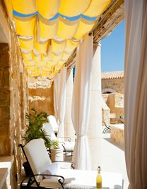 that yellow drapery really pops in this outdoor oasis | tented ceiling shade |