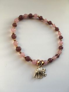 Pretty yet simple purple, pink and rose gold bracelet with a cute elephant charm at the centre. Purple Roses, Pink Purple, Elephant Jewelry, Cute Elephant, Homemade Jewelry, Rose Gold Plates, Friendship Bracelets, Centre, Beaded Bracelets