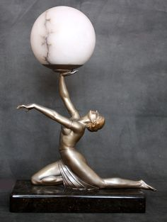 A large classic art deco spelter lamp, circa 1930, Germany.  The cold-painted silver metal figure   mounted on a beautiful dark brown granite base holding aloft   a beautiful Italian alabaster globe  51cm high