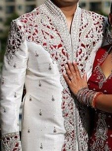 groom's sherwani has underlying red to match the bride's lehenga ...