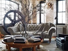 Industrial lighting and decor are balanced by furniture silhouettes in soft shades and warm hues for a cozy and creative approach to loft living.