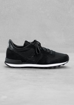 NIKE These black and white sneakers have a retro running shoe style, combining suede and reptile-embossed leather details with nylon upper.
