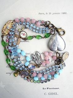 4 Strands Repurposed Bracelet in Pastels with Heart Locket Strands number 3 and 4 are made up of segments from various glass rosaries in pink, baby blue, yummy green. They are interrupted in several places with a vintage gold round scatter pin, a gold cufflink with 3 colors of gold and, quite possibly, a real diamond in the center (!!!), an iris glass vintage connector, and a...