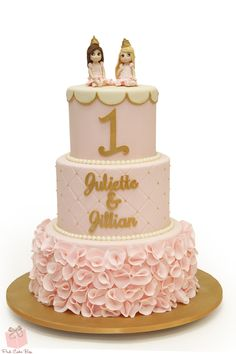 Twin girls first birthday cake.  The princesses were replicated on the top tier and we included pink ruffles on the bottom tier.  Congratulations to the girls!