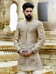 Voguish beige color Indo western invented on khadi with embossed design and high neck collar is adding glamour to the look. Item Code : SIJ6800 http://www.lalitkhatri.com/label/what-s-new/men.html
