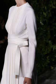 Chic white dress with sharp pleats and crossover belt; fashion details // Valentino