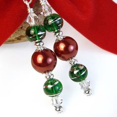 These handmade Christmas earrings are a wonderfully eye-catching combination of red pearls, green glass beads, and Swarovski crystal bicones. Jewelry Logo, Cute Jewelry, Jewelry Crafts, Beaded Jewelry, Men's Jewelry, Jewellery Shops, Jewelry Stand, Jewlery, Jewelry Accessories