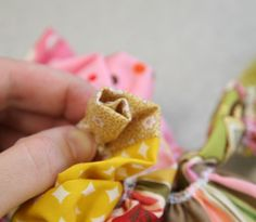 I have a fun new flower tutorial for you that'll use up some of your scraps. Mine is attached to my bag as you can see, and it looks so cute that I almost forget my bag is full of diapers and crumb…