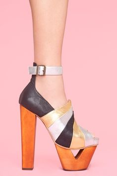 Toweringpeep-toe platforms featuring black, gold and silver leather striped panels.Triangle cutout platform, chunky wooden heel. By Jeffrey Campbell.