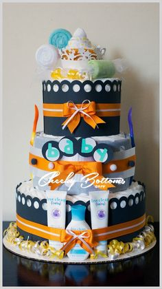 Gender neutral diaper cake with washcloth and bodysuit art as toppers.  This gift is created with: 54 Pampers Swaddlers (size 1), 4 baby washcloths, one baby body suit, 2 baby spoons, one receiving blanket and 3 baby Live Clean products.