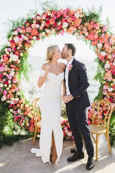 Oh, you gotta love this al fresco destination wedding in Mykonos, Greece with colorful florals and a giant floral hoop. A celebration with an off-the-shoulder bridal gown, floating bulb terrariums and Grecian Wedding, Floral Wedding, Peach Wedding Theme, Coral Wedding Flowers, Wedding Ceremony, Wedding Gowns, Bridal Gown, Wedding Bouquet, Ceremony Arch