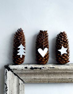 "Pair simple felt or paper christmas shapes with ""snow"" tipped pine cones.  Hang from twine or ribbon. Pinecones"