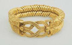 Bracelet with spirally twisted strands and a Heracles knot at the bezel. 2nd century Egyptian, Roman period. gold.