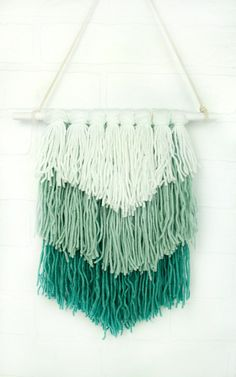 You will definitely capture the Anthropologie and Urban Outfitters vibe with this super simple woven wall hanging. Using just a few $1 rolls of yarn, you can create this awesome DIY wall decor piece.