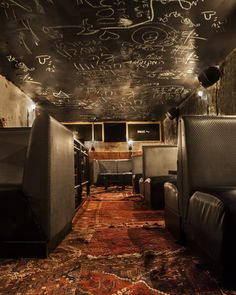 What an interesting mix of finishes.  Chalkboard ceiling and old rugs paired against leather