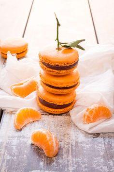Macarons clémentine/chocolat. Ingrédients : 150 g de chocolat noir -100 de crème fraîche liquide entière-5/6 clémentines(corses de préférence-1 ou l'on récupère le zeste, 2/3 pour le jus et le reste pour les suprêmes)-150 g de sucre en poudre-150 g de poudre d'amandes-150 g de sucre glace-110 g de blancs d'œufs liquéfiés à température ambiante-37 g d'eau-1 pointe de couteau de colorant orange-le zeste d'une clémentine. Recette sur le site.