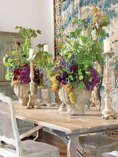 Transitional Blooms Antique stone planters from Chateau Domingue hold grapes, muscari, artichokes, dahlias, hydrangeas, euphorbias and sarracenias.