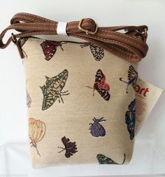 Small tapestry crossbody messenger shoulder bag with a Butterfly pattern faux leather adjustable shoulder strap The bag fastens with a zip to the top