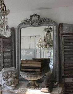 White & Gray Patina  old shutters used to flank a carved mirror over a dresser....charming...