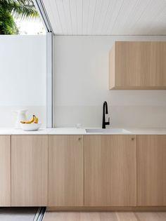 Black and white modern kitchen counter design in an indoor-outdoor kitchen design in Sydney by Benn + Penna Architecture | Remodelista