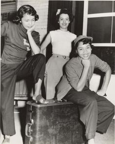 Three women, one wearing dark sweater with two daschund appliques, posed around a suitcase in front of brick building, 1940s.