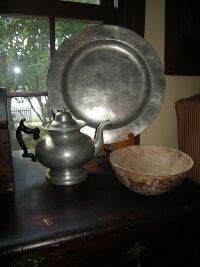 """An early unsigned pewter charger with a 15"""" diameter and a circa 1832-1838 pewter teapot with a J.B. Woodbury touchmark on its bottom."""