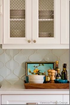 like some metal chicken wire backing; white kitchen with Caesarstone Frosty Carrina countertops, arabesque tile backsplash, chicken wire cabinet fronts, mixed hardware Transitional Decor Kitchen, Decor, Kitchen Design, Country White Kitchen, Kitchen Decor, Kitchen Countertops, Kitchen Tiles Backsplash, Kitchen Style, Trendy Kitchen