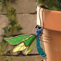 Green Dragonfly Pot Decor    Beautiful flower pot ornaments, made to look as if a Dragonfly has landed on your flower pot. Handcrafted in vibrant, lifelike tones.