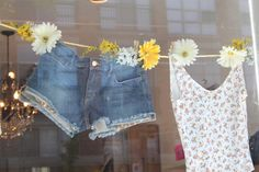 So simple, so word-of-mouth-y! TGtbT.com highly recommends this summer consignment or resale shop window display. Clothes, clothesline, clothespins disguised with big bold fabric daisies! 'summer of love' window display