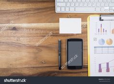 Working Wood Table With Keyboard, White Empty Note Paper, Smart Phone, Pen And Analyze Business Chart. Top View With Copy Space…