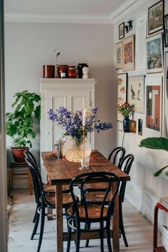 Variety of frames and type of prints. large flower vase on dining table, plants on stands