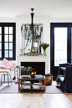Monochrome living room: black painted window frames and door frames, black chandelier, white walls and fireplace, bevel-edged mirror, timber floorboards
