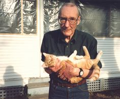 """William S. Burroughs holding his cat Ginger in the backyard of his home in Lawrence, Kansas / Author William S. Burroughs made his love for all things feline known in his book The Cat Inside, in which he refers to cats as """"psychic companions"""" and innate """"enemies of the state."""""""