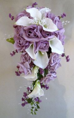 "Bridal cascading Bouquet is design with approx 9 white / cream latex calla lilies,10 large lavender roses,6 medium lavender roses, purple babies breath & approx 24 stems clear gemstones. (optional )     Hand wrapped with lavender & purple satin ribbon.    It measures approx 12"" across and 23"" long."
