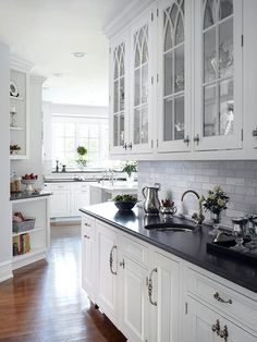 arched glass front cabinets -soapstone countertops.. white kitchen done right!