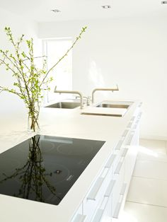 The island functionality is extend to either side with the unique design feature of locating the sinks back to back each with its own bulthaup tap. The Quooker hot water tap straddles the centre and is accessible from either sink. The flat, flush fitting induction hob is the the ultimate in minimalist cooktop design; not only easy to keep clean but also serves as a functional part of the work surface when not in use. Kitchen by bulthaup Winchester.