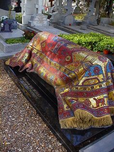 Mosaic Rug  On Rudolf Nureyev's Grave - In 1996 his friends and admirers built a beautiful memorial to Nureyev in the shape and colors of the oriental kilim rugs he had loved to carry with him. The mosaic, designed by his artist friend Ezio Frigerio, is made of mosaic tiles of several shades of red, blue and gold.