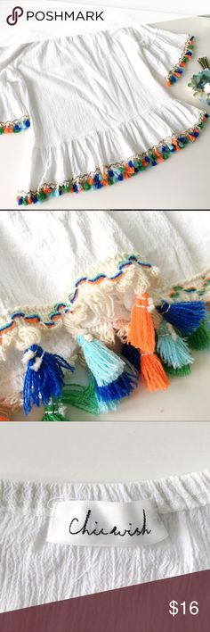 White Off Shoulder Top with Colorful Tassels This off the shoulder shirt is super trendy with multicolor tassels on the sleeves and hem! Perfect for warm weather, vacation, your honeymoon, a cruise, or just to get some sun on those shoulders! One tassel is missing on the backside of the hem, but it is not noticeable when worn. Otherwise it is in very good used condition. From Chicwish. It was originally marked as a S/M, but in my opinion it fits more like a medium. Please see photos for…
