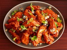 Buffalo Supreme (No. 2) : Dredge the wings in flour and deep-fry. Toss with 6 tablespoons melted butter, 1/2 teaspoon celery salt and 1/2 cup Buffalo wing hot sauce, 2 tablespoons celery leaves and 1 cup crumbled blue cheese. Serve with celery sticks and blue cheese dressing.