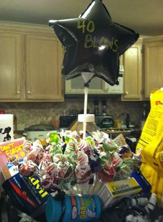 40 gag gift all from dollar tree I lucked out with graduation session for the black colors what you need: 40 blow pops ,Basket,Black Tissue Paper, flower foam,giant pill box,muscle rub, laxatives,gas relief,advil,denture cream, balloon on a stick,ribbon. line basket with tissue paper, put foam in middle & cover w /blow pops & baloon write 40 blows(or 40 sucks), (the ribbon I bought a black and white curly bow)  cut off the black curlies to tie  on other items and place around pops! Gag Gifts, Party Gifts, 40 Blows, Gas Relief, Balloon Gift, Black Colors, Practical Jokes, Graduation Day
